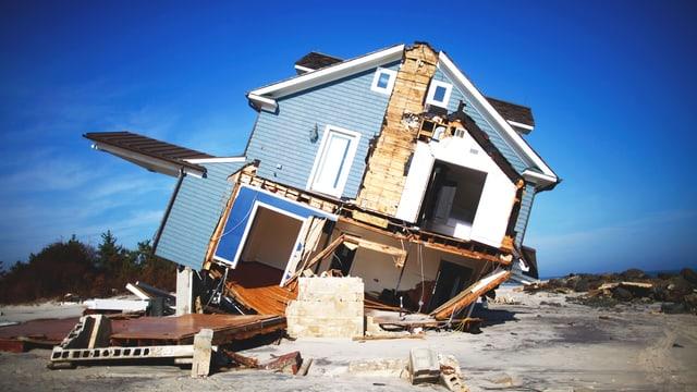 Sturmgezeichnetes Haus, das zur Seite gekippt ist.