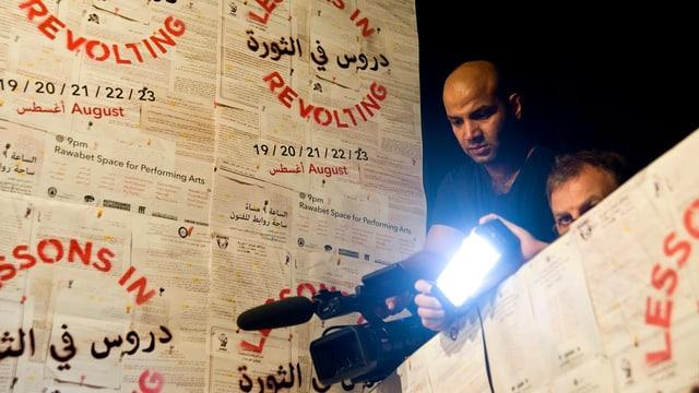 Zwei Filmemacher stehen auf einer Tribüne, wobei der eine die Kamera ausrichtet und der andere einen Scheinwerfer hält.