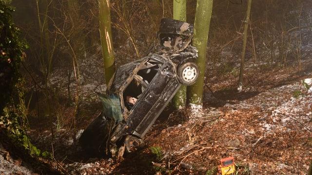 Ein total zerstörtes Auto in einem steilen Waldstück.