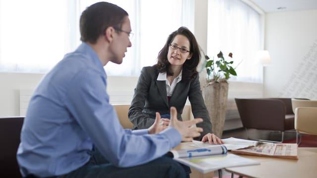Ein Mann und eine Frau im Gespräch an einem Tisch mit Unterlagen