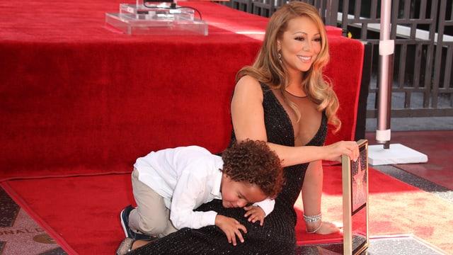 Sängerin Mariah Carey liegt neben ihrem STern auf dem Walk of Fame. Ihr Sohn klettert auf ihr rum.