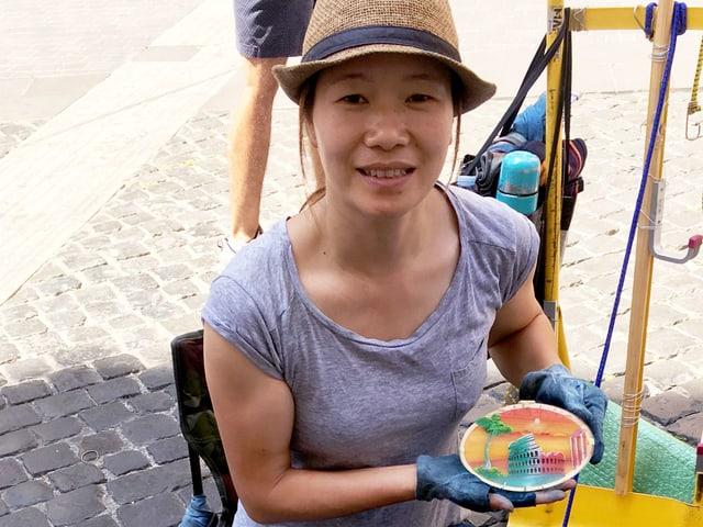 Stella Chun verkauft in Rom ihre handgemalten Bilder.