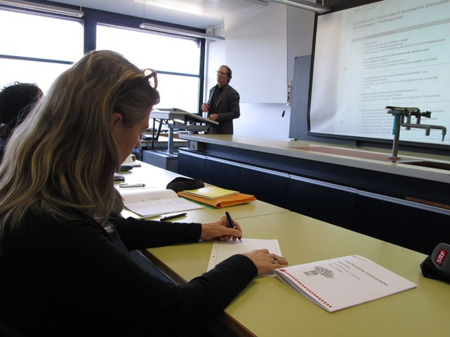 Ein Lehrer referiert neben einer Leinwand.