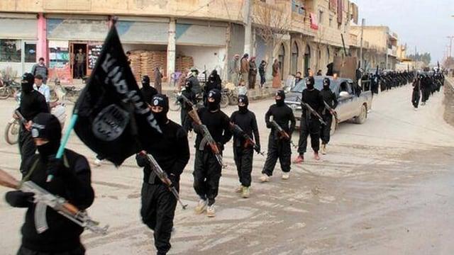 Schwarz vermummte Männer mit Gewehren marschieren durch eine syrische Stadt.