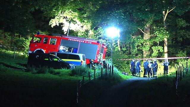 Feuerwehrauto in einem Waldstück in der Nacht. Flutlichter brennen.