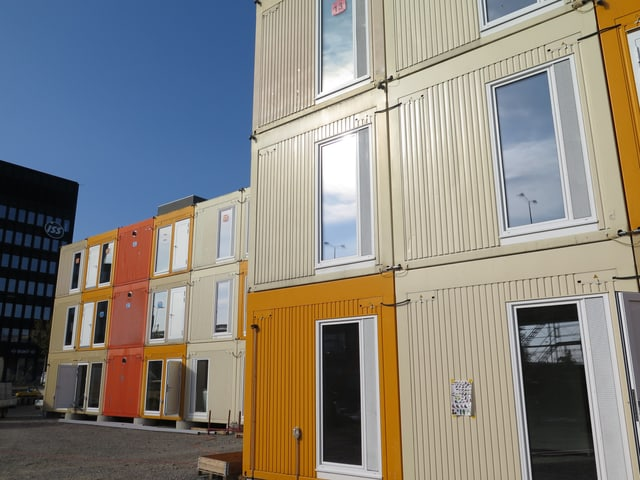 Eine Containersiedlung - mit orangen und beigen Containern. Dahinter der blaube Himmel.