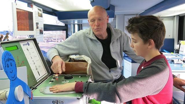 Dominik Jeckelmann erklärt einem Schüler im Bus ein Experiment.