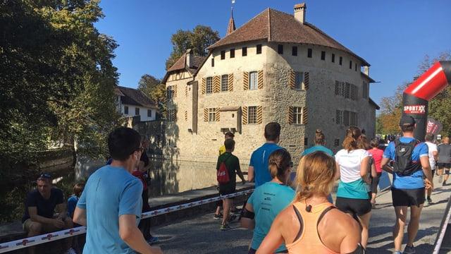 Läuferinnen und Läufer laufen auf das Schloss Hallwyl zu