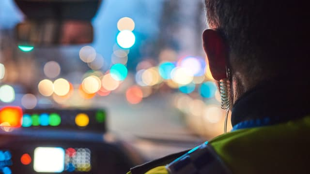 Bild von hinten in einem Auto nach vorne. Man sieht den Kopf eines Polizisten und die abendlichen Lichter in der Frontscheibe.