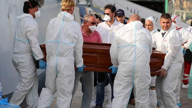 Männer, die einen Holzsarg aus einem Schiff ausladen