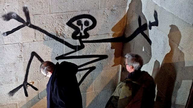 Eine Strichfigur auf einer Steinmauer, zwei Männer laufen daran vorbei.