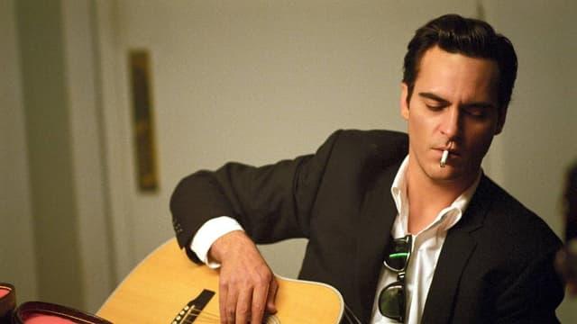 Ein Mann mit einer Zigarette im Mund spielt Gitarre.