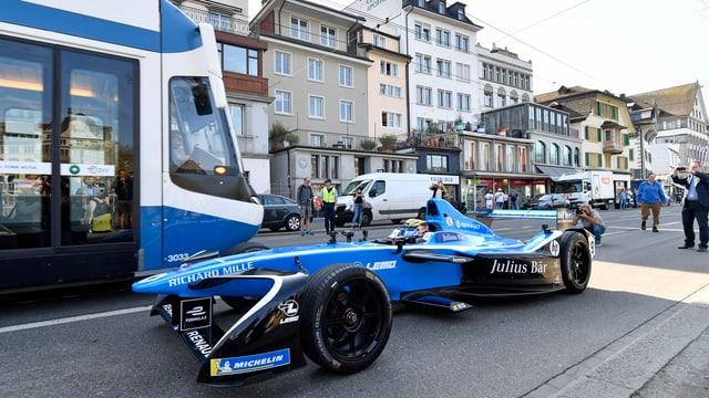 Formel-E Wagen fährt vor blauem Zürcher Tram durch