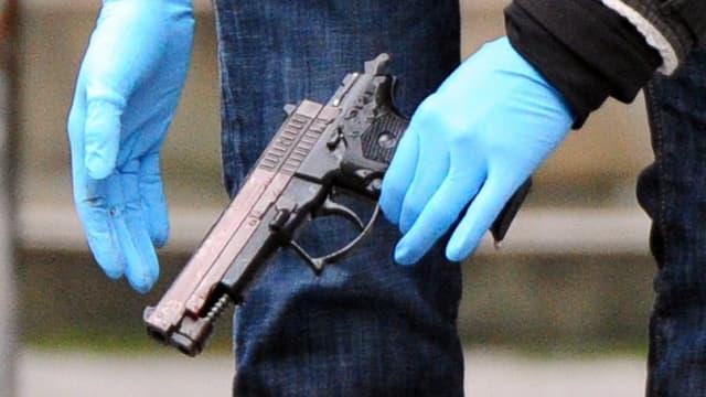 Eine Beamtin mit Handschuhen hält die vermeintliche Tatwaffe in Händen.