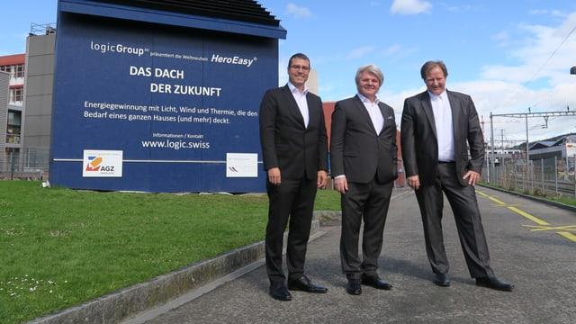 Drei Männer in Anzügen vor einem blauen Häuschen.