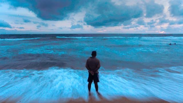Mann steht am Meer und schaut zum Horizont