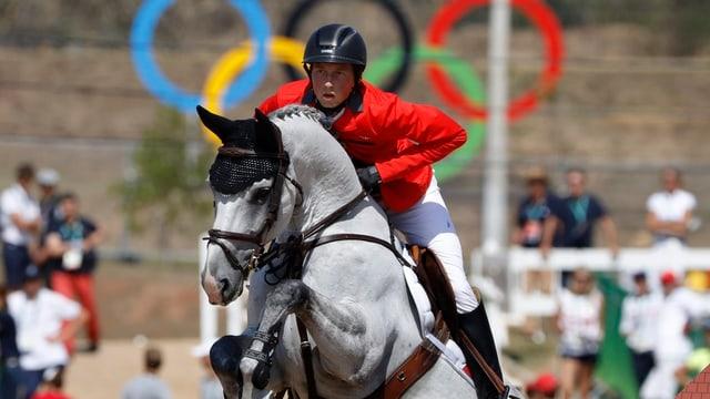Martin Fuchs springt mit seinem Schimmel in Rio über ein Hindernis. Im Hintergrund sind die Olympischen Ringe zu sehen.