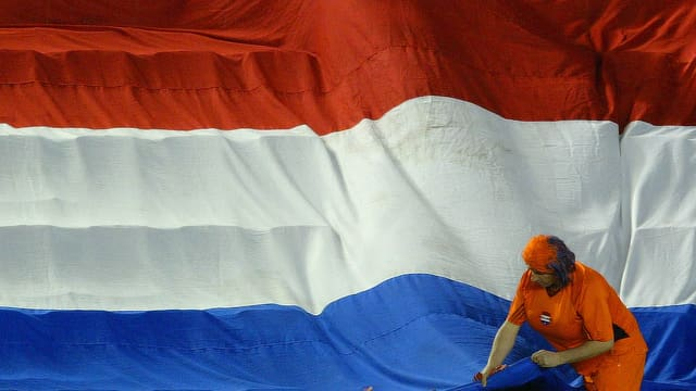 Eine orange gekleidete Frau vor einer niederländischen Flagge.