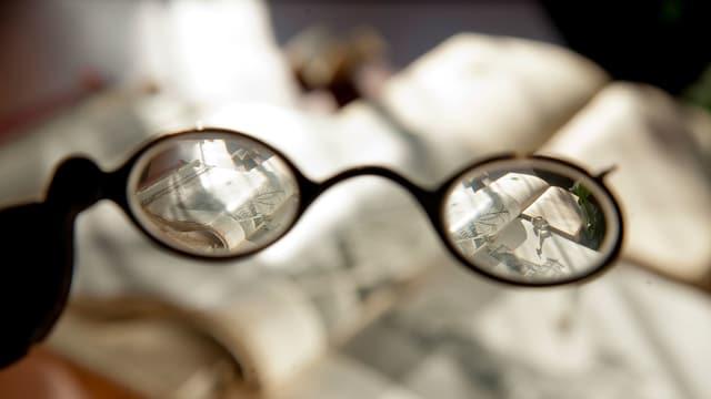 Symbolbild: Durch eine Brille auf Bücher blicken.