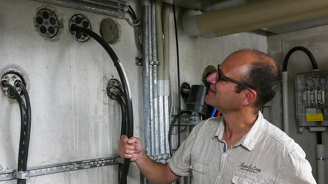 Reto Widmer von SRF Digital umfasst mit einer rechten Hand das 25mm dicke Bodensee-Glasfaserkabel, das beim Fährhafen Konstanz landet.