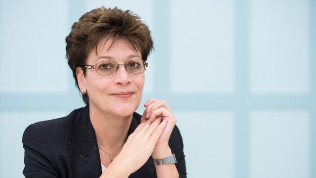 Eine Frau mit Brille und kurzen Haaren blickt in die Kamera.