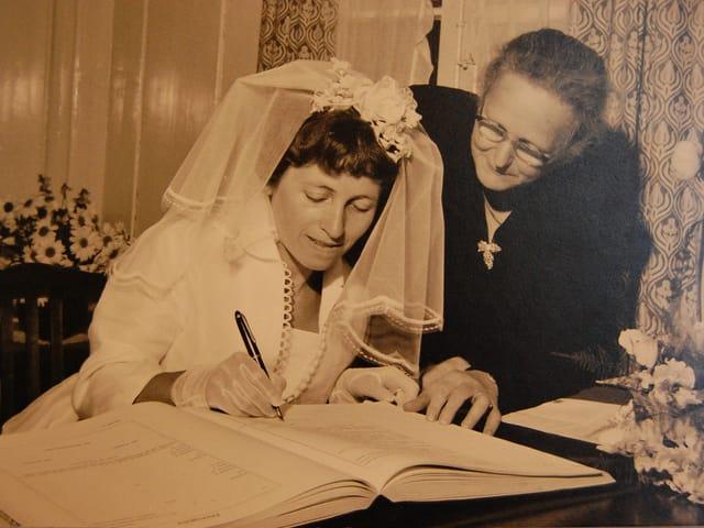 Eine Braut unterschreibt im Hochzeitsbuch.