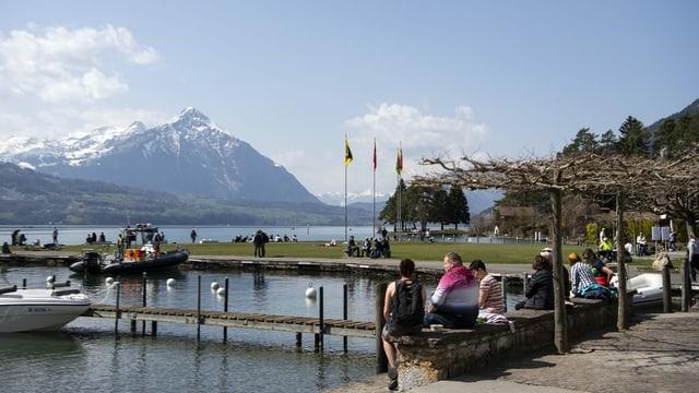 Leute sitzen in Interlaken am See auf Bänkli im Hintergrund der Niesen