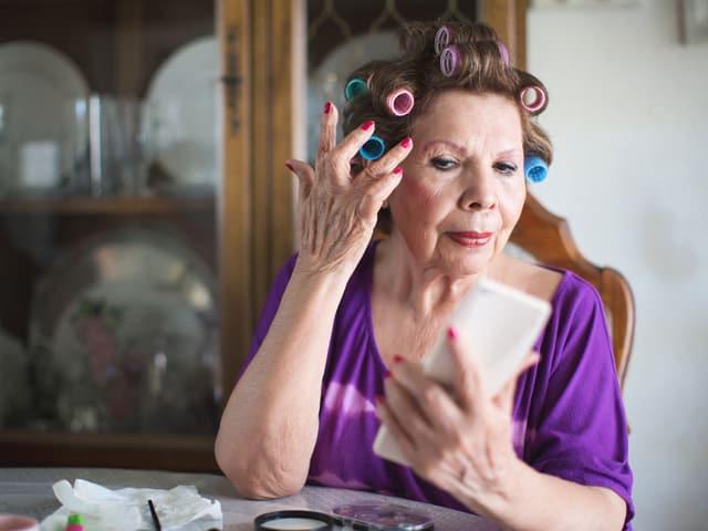 Eine ältere Frau zupft Ihre Haare zurecht, die in Lockenwicklern stecken.