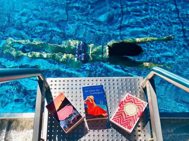 Annette König schwimmt in einem leuchtend blauen Schwimmbecken. Im Vordergrund sind die Bücher von Jane Austen, Elizabeth Jane Howard, Rosamunde Pilcher zu sehen.