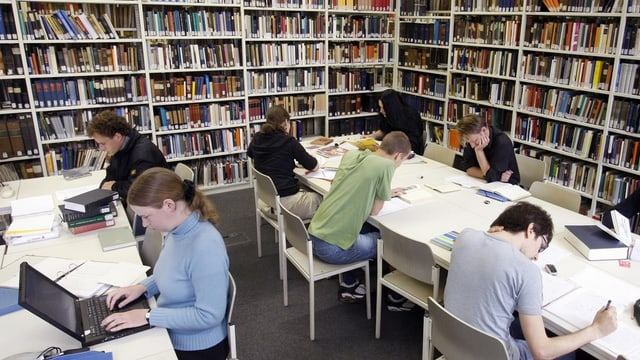 Studentas e students lavuran en ina biblioteca.