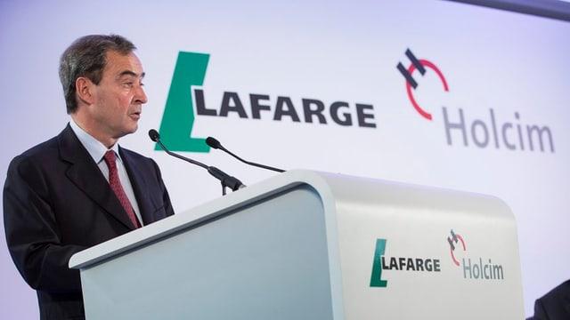 Bruno Lafont, il CEO da Lafarge discurra avant in pult cun si il loga dals dus concerns.