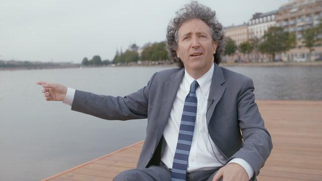 Auf dem Bild ist James Ehrlich neben einem Gewässer zu sehen wie er auf etwas zeigt.