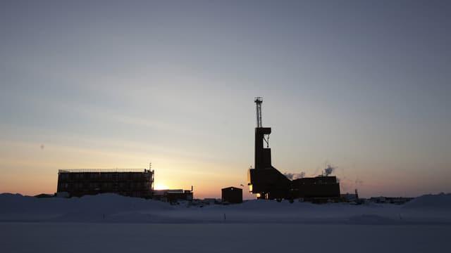 Sonnenunternang hinter einem Bohrturm in Prudhoe Bay.