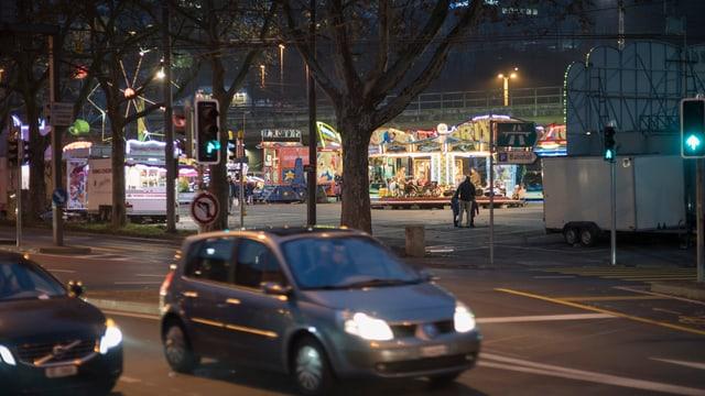 Die Schützenmatte in der Nacht, die Lichter des Lunaparks und davor auf der Strasse Autos.