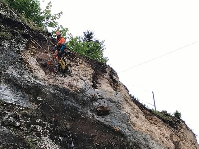 Kletterer an Seil in Felswand.