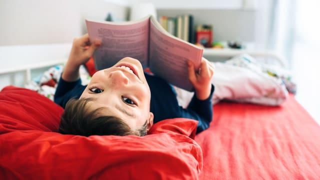 Ein Bub liegt im Bett und liest.