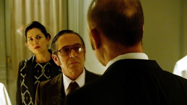 Mann mit grosser Brille (frontal) schaut einem andern Mann ins Gesicht (von hinten sichtbar). Hinten im Bild steht zudem eine Frau.