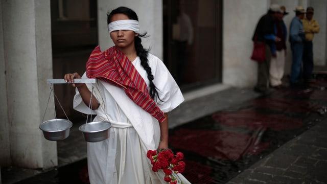 Eine Frau in Justitia-Kostüm mit Balkenwaage in der Hand.