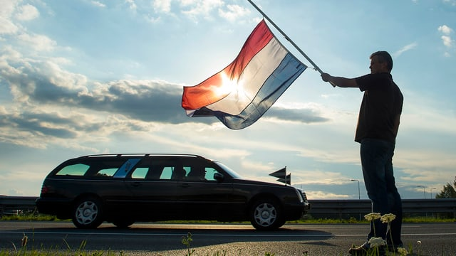 Ein Niederländer steht mit einer Flagge auf Halbmast, während Opfer des Flugzeugabsturzes vom Flughafen Nieuwegein in die Gerichtsmedizin transportiert werden. (reuters)