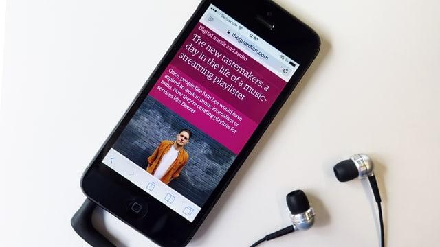 Ein Smartphone liegt neben Kopfhörern auf einem tisch. Auf dem Bildschirm sieht man ein Bild eines jungen Mannes.