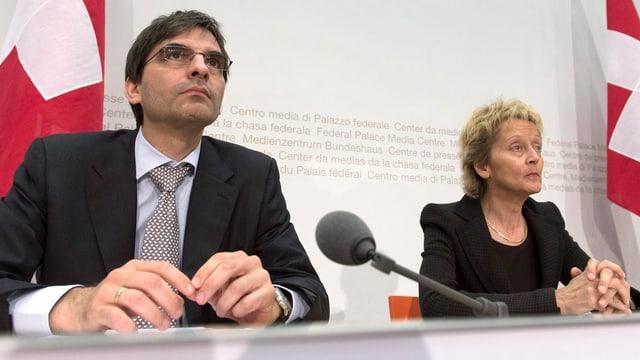 Brunetti sitzt links, Widmer-Schlumpf rechts, dahinter Schweizer Fahnen.