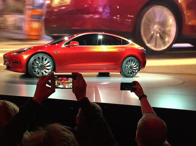 Zuschauer fotograhieren einen Tesla.