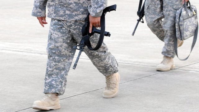 Zwei US-Soldaten (nur die Beine), gehend, in Uniform, mit einem Maschinengewehr in der Hand.