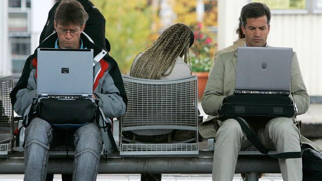 Man sieht zwei Männer, die auf einer Bank sitzen und am Laptop arbeiten.
