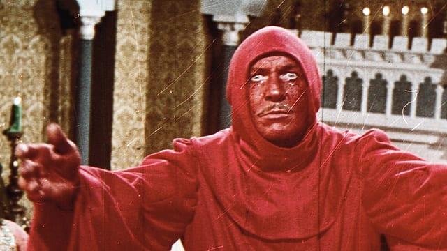 Filmstill: Ein Mann mit rot angemaltem Gesicht in einem roten Kapuzenkleid