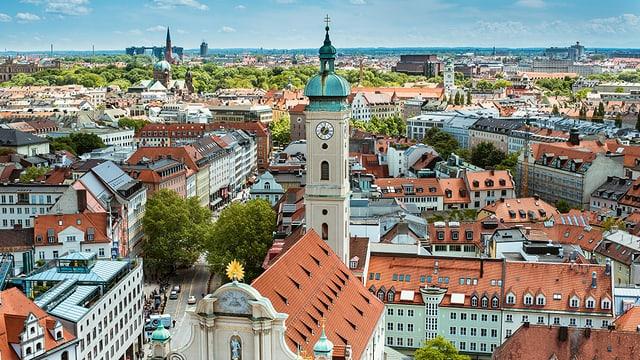Blick von einer Anhöhe auf die Stadt München mit vielen Ziegeldächern und einem Kirchenturm.