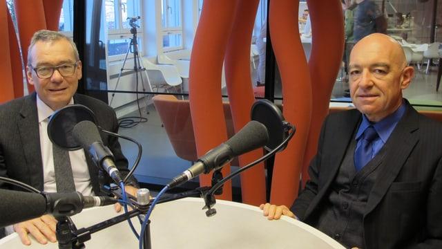 Zwei Männer an rundem Tisch mit Mikrofonen im Radiostudio