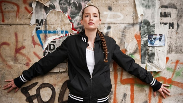 Ein Porträt von Steff la Cheffe: Eine junge Frau mit Zopf über der Schulter steht vor einer Wand mit Graffitis.