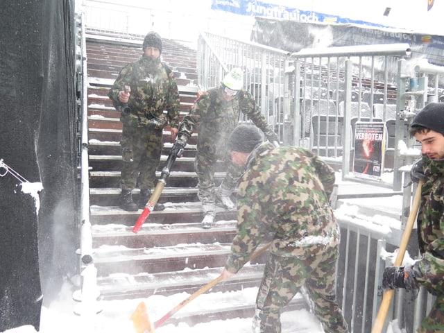 Männer befreien die Tribüne vom Schnee.
