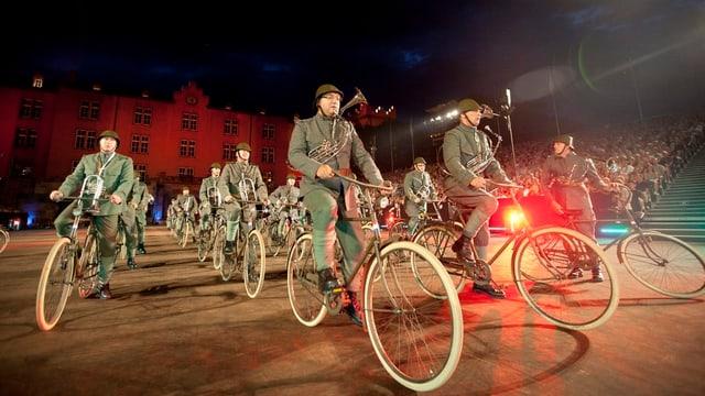Fahrradparade von Militärmusikern auf dem nächtlichen Kasernenareal.